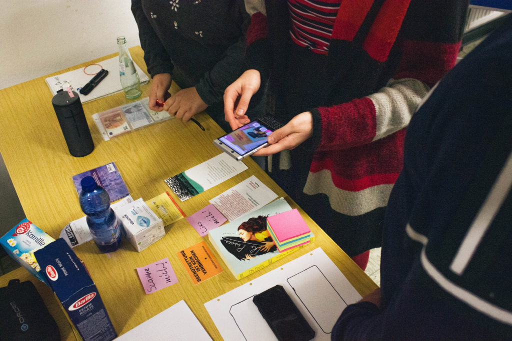 Ein Smartphone wird über einige Gegenstände gehalten, die auf einem Tisch liegen. Die Kamera des Smartphones ist an