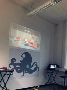 Zu sehen ist ein Filmausschnitt mit einer Playmobil-Figur, der mit Beamer an die Wand geworfen wird, und eine Krake aus Karton