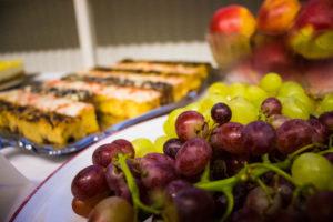 Ein Buffet-Tisch: im Vordergrund Weintrauben, im Hintergrund Kuchen
