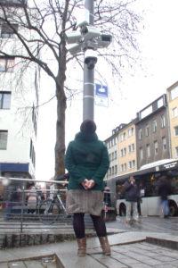Eine Frau steht, mit dem Rücken zur Kamera, vor einem Mast mit vielen Überwachungskameras und schaut hinauf. Ihre Arme sind auf dem Rücken verschränkt.