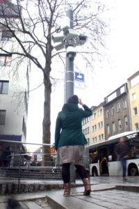 Eine Frau steht, mit dem Rücken zur Kamera, vor einem Mast mit vielen Überwachungskameras und schaut hinauf. Sie kratzt sich am Kopf.
