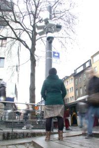 Eine Frau steht, mit dem Rücken zur Kamera, vor einem Mast mit vielen Überwachungskameras und schaut hinauf. Ihre Hände hat sie in die Jackentaschen gesteckt.