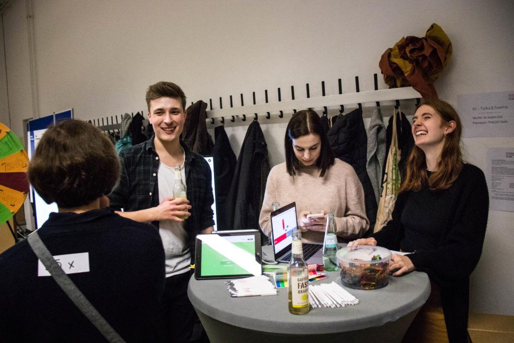 Drei Studierende stehen um einen Stehtisch und lachen, im Hintergrund ist ein Glücksrad