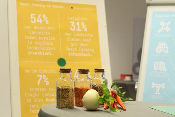 Ein Stehtisch mit Postern über Smart Farming im Hintergrund