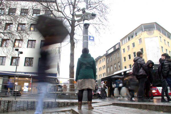 Eine Frau steht, mit dem Rücken zur Kamera, vor einem Mast mit vielen Überwachungskameras und schaut hinauf. Ihre Arme hängen an den Seiten herunter.