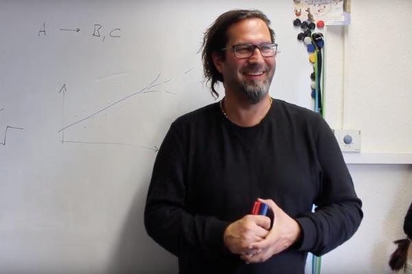 Prof. Heisenberg steht vor einem Whiteboard, auf das er etwas geschrieben hat
